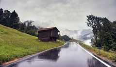 On a rainy day in the Swiss Alps (PeterThoeny) Tags: schuders pusserein schiers swissalps switzerland grisons prättigau road rain wet barn building house tree day outdoor cloud clouds cloudy sky mountain landscape reflection water wetreflection symmetry 3xp raw nex6 photomatix selp1650 hdr qualityhdr qualityhdrphotography grass field fav200