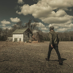 A man walking in a open field towards an old house in a rural area of Frankford, Delaware, in a sunny day with blue sky and dramatic clouds. (pedferr) Tags: sunny cinematic woods fashion 1x1 moody hat unitedstatesofamerica tree outdoors farm dramatic usa building jeans mensfashion old delaware wooden vintage rural boots walking clouds sweater style man selfportrait warm scene model landscape winter nature male house lifestyle sky field