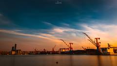 Landscape #4 (knellwang) Tags: city longexposure ship shipyard dusk sunset sea seaside orange sky cloud stack skyline landscape fujifilm photography china dalian building sunny lighting shadow