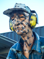 Ear Protection (Steve Taylor (Photography)) Tags: earprotection cap art sculpture metal newzealand nz southisland canterbury christchurch cbd city avonsidedrive container hannahkidd mall mower restart steel corrugatediron welds shirt blue white yellow brown man lines