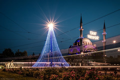 Lights and Trams (Anthony P.26) Tags: art category eskisehir lighttrails places travel turkey city cityscape mosque minaret lights lightstars evening dusk trams transport garden plants flowers flowerbed canon canon1585mm canon70d outdoor architecture placeofworship tracks lines electricity power fence bushes roses building dome sky statue