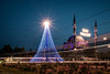 Lights and Trams (The Frustrated Photog (Anthony) ADPphotography) Tags: art category eskisehir lighttrails places travel turkey city cityscape mosque minaret lights lightstars evening dusk trams transport garden plants flowers flowerbed canon canon1585mm canon70d outdoor architecture placeofworship tracks lines electricity power fence bushes roses building dome sky statue