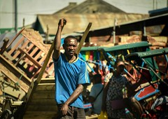 Market Worker (Rod Waddington) Tags: africa african afrique afrika madagascar malagasy market worker handcart buildings streetphotography street man rickshaw woman furniture outdoor job