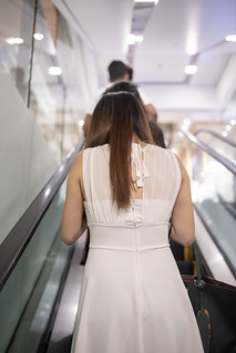 Young woman in white dress moving up on escalator