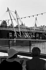 The Travellers - London, UK (Sandrine Vivès-Rotger photography) Tags: london uk england thames blackandwhite bridge southbank tourists travellers couple friends portrait streetlife streetphotography southoftheriver talking people lights