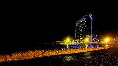 W - Over the slim wave (Fnikos) Tags: beach sand shore seashore sea wave water waterfront city sky skyscraper night nightview building architecture tower tree palmtree light colour outdoor