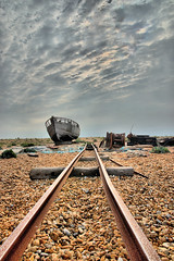 Rails to the Sea (Geoff Henson) Tags: boat wreck rails beach clouds sky sea water stones debris