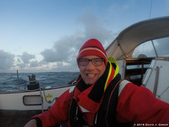 Happy for Blue Skies (David J. Greer) Tags: north atlantic ocean winter crossing passage storm sailboat rubicon3 sailtrainexplore oriole bowman cockpit guy male man smiling hat life jacket glasses sunset dusk onboard sailing winch blue sky clouds dodger sitting