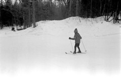 121069 10 (ndpa / s. lundeen, archivist) Tags: nick dewolf nickdewolf december photographbynickdewolf winter greenville maine mooseheadlake snow blackwhite bw 1969 1960s monochrome blackandwhite skitrip bigsquaw bigsquawmountain bigsquawmountainresort 35mm film skiing people skier slopes trail run child skis trees poles coat jacket boots skipoles hat girl nicole gloves