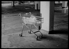 shopping trolley in multistorey carpark underneath scheduled for demolition Milford Towers, Catford (dmc101) Tags: subminiature grain urban city carpark shoppingtrolley lewisham derelict abandoned noir unexplained hp5 ilford homedeveloped ilfordddx monochrome blackandwhite 16mm film minolta16 documentaryphotography