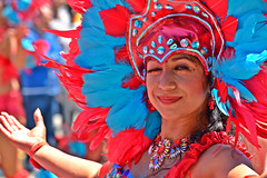 Wink (TheseusPhoto) Tags: colorsoftheworld colors costume people candids candid streetphotography street pretty girl woman festival carnaval latino sanfrancisco california culture feathers