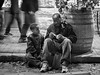 Father and Son (Anne Worner) Tags: anneworner blackandwhite em5 father georgetown olympus son texas bw barrell black boy candid downtown eating man mono people sidewalk sitting street streetphotography talking together two communicating family ivy plant growing candidstreetphotography outdoors outside availablelight silverefex walking motion jeans jacket sneakers food lensbaby composerpro sweet35 manualfocus manualfocuslens selectivefocus