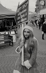Job satisfaction. (ianmiller6771) Tags: job satisfaction blackwhite streetphotographyuk expression costume billboard girl christmas candid boredom fuji 35mm heavymakeup pointedhat fingernails resignation unhappy bw blackandwhite ukstreetphotography streetportrait mrssantaclaus streetphotography streetmarket