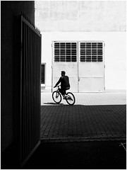 Through the Finish Line (Thomas Listl) Tags: thomaslistl blackandwhite noiretblanc biancoenegro street urban biker bicycle entrance lightandshadow contrasts door garage yard würzburg 50mm