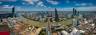 Aerial view of Bangkok skyline and skyscraper with light trails on Sathorn Road center of business in Bangkok downtown. Panorama of Taksin Bridge over Chao Phraya River Bangkok Thailand with blue sky and clouds.