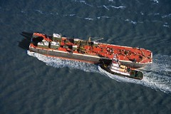Stock Images (perfectionistreviews) Tags: usa newyork photograph colour color image horizontal highangle birdseyeview viewfromabove aerialview city travel tugboat transportation water watercraft ship boat twoobjects nobody harbour harbor pusing towing tug watervessel vessel outdoors industry bay powerful fuel oiltanker oiler tanker boats copyspace fueltanker northamerica ships nyc industryandagriculture newyorkcity