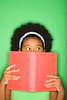 Stock Images (perfectionistreviews) Tags: 1012years kid child female girl onepersononly photograph color africanamerican preteen studioshot indoors portrait studio vertical halflength looking suspicious holding novel education bookworm reading learning book facialexpression expression covering green knowledge lifestyle leisure student school person