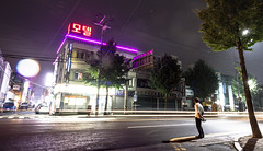 Gyeongju, South Korea 2016 (MonkeyTakingPics) Tags: southkorea korea night gyeongju street rain rainy citylights city streetphotography dark travel canon 7d asia building road sign intersection nightlights people man crossing colors