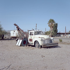 roadside assistance. bouse, az. 2018. (eyetwist) Tags: eyetwistkevinballuff eyetwist bouse arizona towtruck abandoned rusty mamiya 6mf 75mm kodak portra 160 mamiya6mf mamiya75mmf35l kodakportra160 ishootfilm ishootkodak analog analogue film mamiya6 square 6x6 120 filmexif epsonv750pro mediumformat lenstagger desert highdesert landscape roadsideamerica sonorandesert lonely tow twoing truck wrecker derelict decay well drilling bumper classic grille shattered windshield palmtree az72