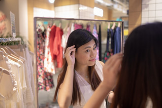 Young woman checking fashion in clothing shop