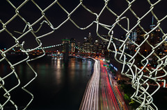 A Downtown View (Gary Walters) Tags: lights night lighttrails hff fence sony a7r2 nyc a7r ii gary walters city cityscape nightscape buildings downtown brooklynbridge a7rii garywalters