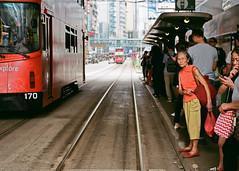 """tram lane ... causeway bay"" (hugo poon - one day in my life) Tags: nikonfe2 nikon50mm18 film fujicolorindustrial400 hongkong causewaybay hennessyroad canalroad tram people waiting"