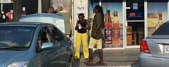 Life Between Cars (Anthony Mark Images) Tags: people portrait streetphotography liquorstore vinars davidandsubs shops thestrip mobay montegobay jamaica westindies caribbean lady men dreadlocks yellowpants