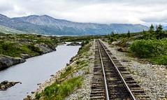 Rugged Alaskan Scenery (Eyes Open To Life) Tags: railroadtracks train alaska landscape yukon skagway rugged wilderness tracks nature mountains lake water ruggedterrrain
