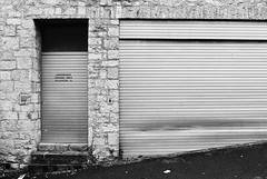 Craftsmen Only (Thomas Listl) Tags: thomaslistl blackandwhite biancoenegro noiretblanc filmphotography minoltax700 kodak tmax push1stop garage silver lines 35mm analog door craftsman schlosgasse