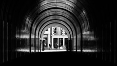 Light At The End Of The Tunnel (Sean Batten) Tags: london england unitedkingdom gb europe city urban blackandwhite bw rathbonesquare streetphotography street light shadow tunnel lines curves nikon df 35mm candid people