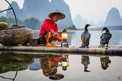 Cormorant Fisherman - Gas Lamp 3 (lc99photography) Tags: cormorantfisherman cormorantfishing cormorant river lijiang liriver mountains birds reflections people red light lamp raft bambooraft guangxi guilin dusk