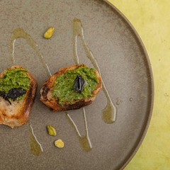 Grilled baguette with pistachio pesto and black garlic. (annick vanderschelden) Tags: bread baguette french oliveoil grilled blackgarlic garlic pottery plate yellow food cooking cuisine rosemary garnish extravirginoliveoil pistachiopesto pesto italy pistachio served belgium
