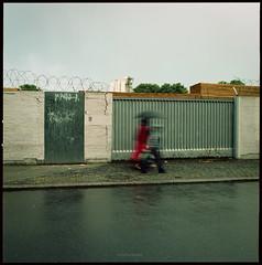 * (Konrad Winkler) Tags: berlinneukölln zaun mauer tor stacheldraht regen str passanten kind langzeitbelichtung hasselblad503cx mittelformat 6x6 epsonv800