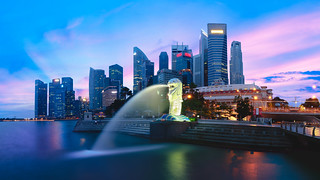 The Merlion fountain lit up at against the Singapore skyline