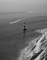 Passersby (Lloyd Austin) Tags: nikon d7200 sigma1750mm mono monochrome grey white black bw blackwhite bnw shoreline rocks chalk cliffs coastal coastline boats sea lighthouse englishchannel england eastsussex eastbourne beachyhead passersby