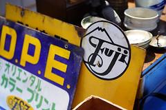 """Fuji"" (Eric Flexyourhead) Tags: minami minamiku 南区 kyoto 京都市 kansai 関西地方 japan 日本 toji 東寺 japanese temple market fleamarket antique antiquemarket sign signboard vintage retro showa fuji yellow blue sonyalphaa7 zeisssonnartfe55mmf18za zeiss 55mmf18"