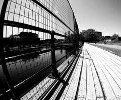 Lachine Canal Boardwalk (MassiveKontent) Tags: streetphotography bwphotography streetshot architecture geometric lines symmetry bw contrast city monochrome urban blackandwhite streetphoto shadows boardwalk lachinecanal gopro fisheye noiretblanc blackwhite montreal montréal quebec fence blancoynegro