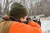 Stock Images (perfectionistreviews) Tags: 2025years adult horizontal image photograph color outdoors onepersononly safety blazeorange camo camouflage caucasian headandshoulders hunting lifestyle leisure midadultman orange recreation safetyorange sport shotgun beard snow trees nature gun aim beanie gloves cold winter lifestylesandart