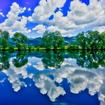 Kreutsee with tree and cloud reflections in Bavaria, Germany thumbnail