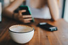 Coffee cup in focus. Hand holding a phone in the background. (wuestenigel) Tags: drinking enjoying mug copy beverage table space background hand hot female away girl take woman cafe fresh business disposable white cup restaurant people young vintage hands coffee tea takeaway hipster cappuccino drink holding warm focus bar break friends home object modern morning paper couch breakfast