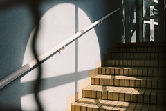 Searchlight (Thomas Listl) Tags: thomaslistl color filmphotography minoltax700 fuji pro400h fujipro400h analog 35mm lightandshadow light stairs staircase lines handrail curves cross circle blue wall door