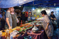 Couple buys traditional Thai street food (Evgeny Ermakov) Tags: asia asian chiang chiangmai mai southeast southeastasia thai thailand barbecue bbq buy buyer buying candid city citylife couple crowded cuisine culture cultures customer delicious destination dish dishes exotic famous fastfood food foodcart foodcourt foodstall landmark man market marketplace meal men night nightmarket people salesman saturdaymarket sell stall street streetfood sundaymarket takeaway tourism tourist touristic tourists traditional travel typical vendor walkingstreet weekend woman women work yum yummy editorialuse