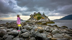On the rocks - Rugged West Coast (Christie : Colour & Light Collection) Tags: park outdoors westcoast westvancouver bc canada beach shoreline shore britishcolumbia oceanside ocean rocks stones island nikon nikkor photography stormy cloudy clouds cloudwork trees pacificnorthwest whytecliff whytecliffpark lead bolder contrasting ngc vancouver islet child pink yellow