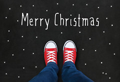 Feet wearing red shoes on black background with Merry Christmas text (TheHouseWire) Tags: shoes hippy sneakers red retro step student way journey blackboard jeans youth direction relax feet background copyspace choice concept urban guide lifestyle standing blue empty space road redcanvassneakers pair start beginning christmas text year type holiday chalkboard chalk