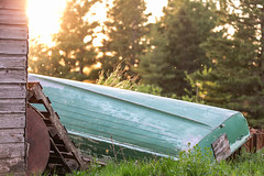 Old Boat (Jenna.Lynn.Photography) Tags: boat summer sun golden hour storage patched green grass shed junk country rural trees sunset rays upsidedown landscape junkpile object