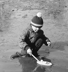 Simple fun (theirhistory) Tags: children kids boy boat ship water puddle hat cap jacket trousers wellies rubberboots