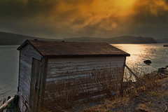 Old Shed - Dunville (Dolores Harvey) Tags: dunville placentia newfoundland sun sunset dramatic old historic fishing stage doloresharvey deloresharvey canvassingtheneighbourhood canvassingtheneighbourhoodcom canvassingtheneighbourhoodphotography lean orange water ocean sea autumn sky dramaticsky cloudy reflections nature storage