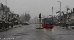 Route W11 Snow (M C Smith) Tags: junction pentax k3 chingford route w11 bus red letters numbers symbols snowing pylons houses telegraphpoles lamps pavement kerb grey lights reflections cars traffic railings wall hedges green yellow walls tree branches black brown pylon wires busstop