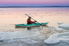Man navigates in kayak alone on icy Ontario winter lake (blurMEDIA Stock) Tags: brucepeninsula canada earth georgianbay ontario pfd active carpediem challenge climate climatechange determination environment environmental exercise fitness frozen fun globalwarming goodlife happy health healthy ice icy journey kayak kayaking lake lifejacket lifestyle living north northern outdoor perserverance planet refreshing rejuvenation relaxation retreat safety seasons skill solitary solitude sport warming winter wintersport