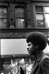 111770 32 (ndpa / s. lundeen, archivist) Tags: nick dewolf nickdewolf photographbynickdewolf blackwhite bw monochrome blackandwhite 35mm film boston massachusetts november 1970 1970s citylife streetlife streetphotography candid people city downtown man youngman black africanamerican afro natural profile buildings awning business store shop hairstyle